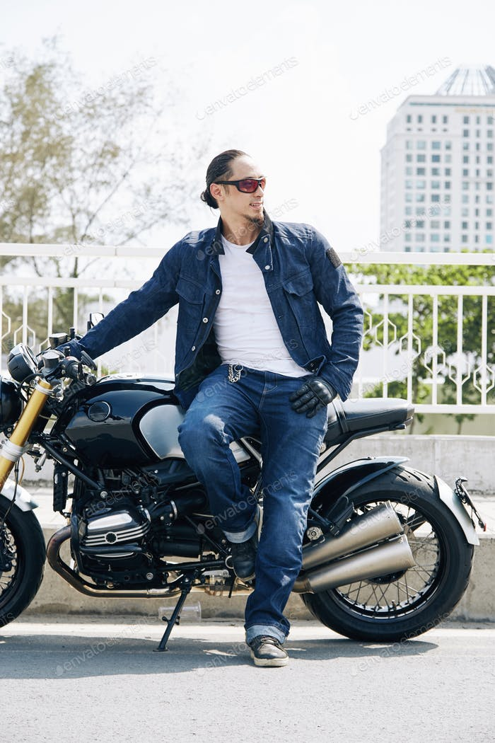 Stylish motorcyclist in jeans and jacket