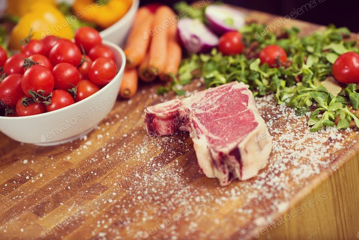 Juicy slice of raw steak on wooden table