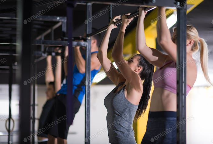 young athletes doing pull ups on the horizontal bar