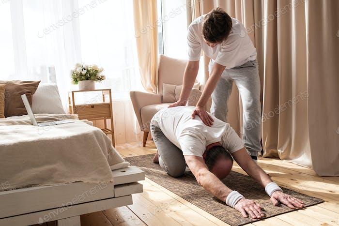 Yoga-Trainer hilft älteren Männern, Yoga Asana Balsana richtig zu Hause zu machen.