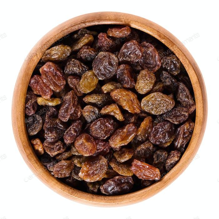Dark brown raisins in wooden bowl over white