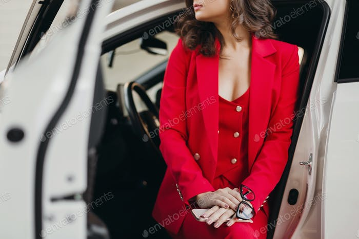 beautiful sexy rich business woman in red suit posing in white car