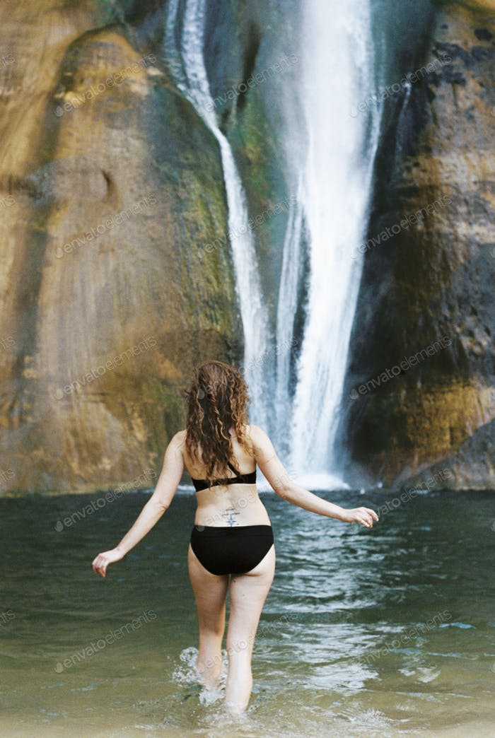 Woman in a black bikini wading into a pool with a waterfall cascade tumbling down a cliff.