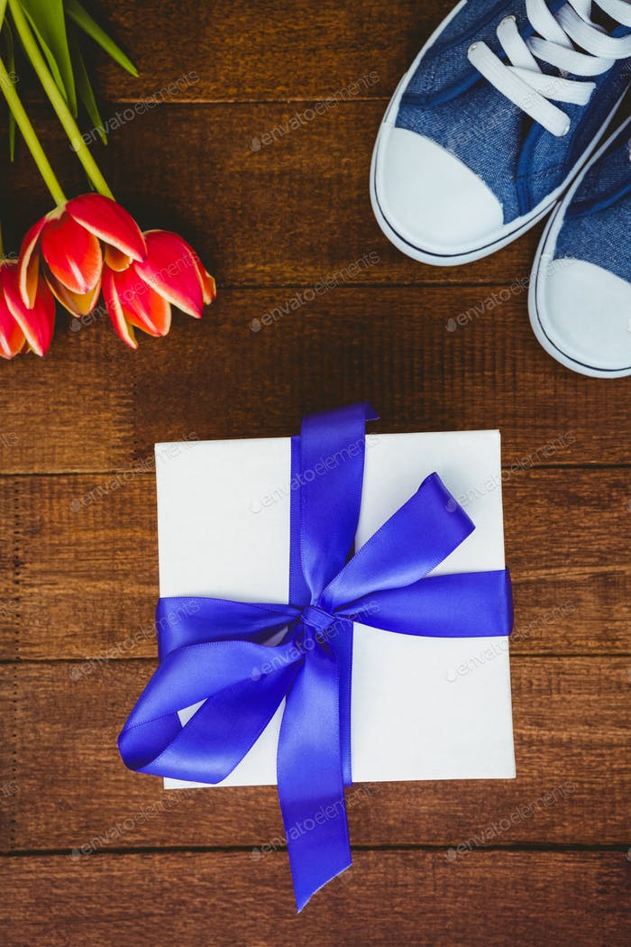 close up view of sneakers and blue gift