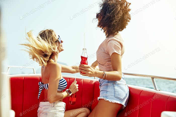 Two women having fun on a boat during summer vacation
