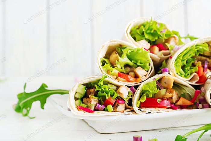 Mexican street food fajita tortilla wraps with grilled  chicken fillet and fresh vegetables.