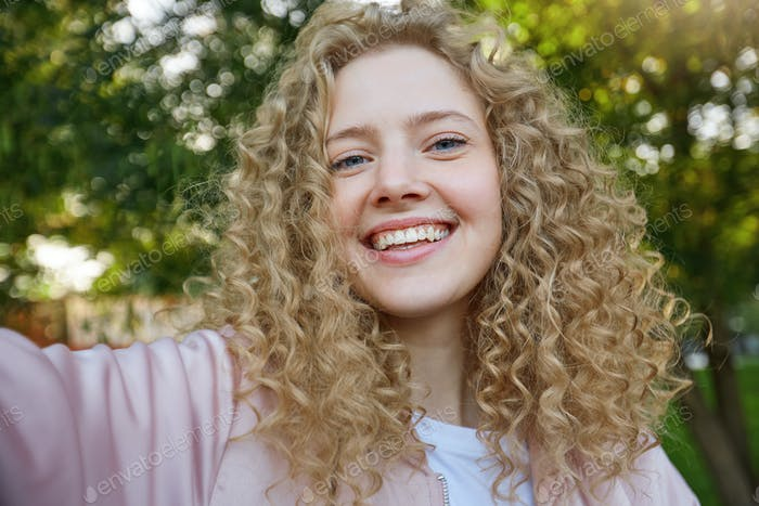 Selfie-portrait of charming young beautiful blonde girl with curly hair, in a great mood