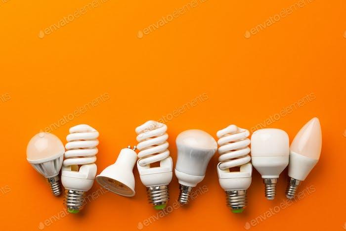 Muchas bombillas sobre fondo naranja brillante