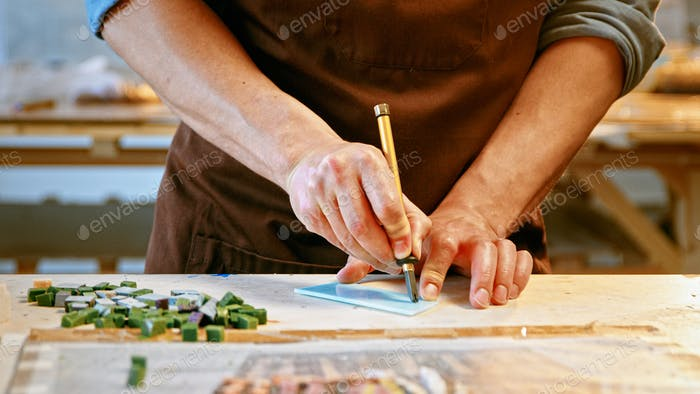 Male hands cutting a piece of glass in creative workshop