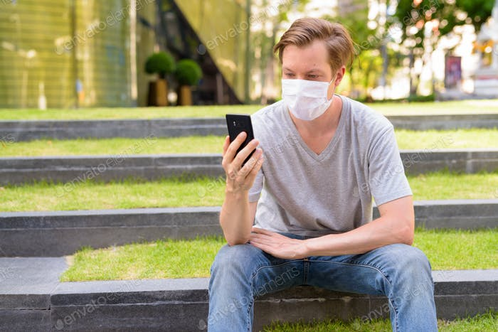 Young man with mask for protection from corona virus outbreak using phone while sitting outdoors