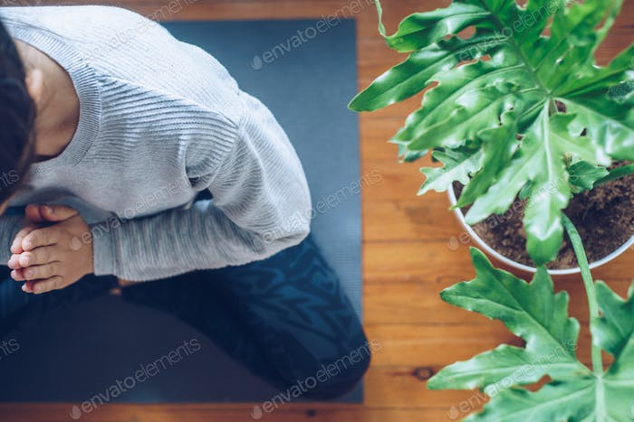 Woman doing yoga in the morning at her home, top view.