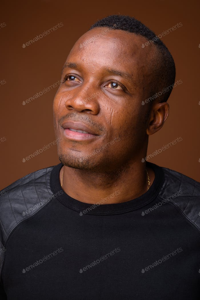 Studio shot of young African man against brown background