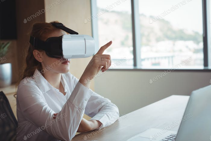 Businesswoman using virtual reality technology in office