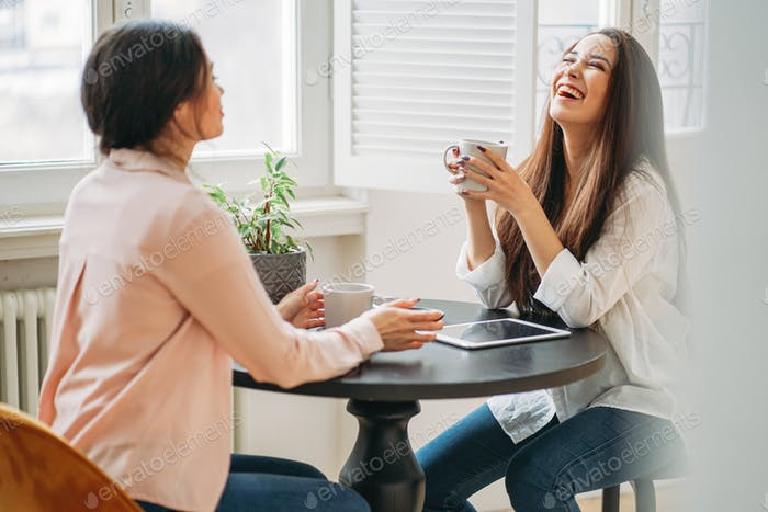 Young carefree brunette girls friends in casual with cups of tea meeting in bright cafe