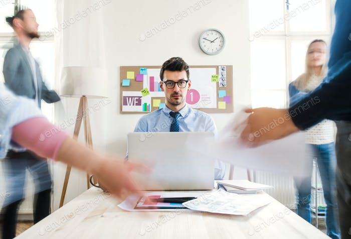 Young businesspeople in a modern office, having meeting. Motion blur.