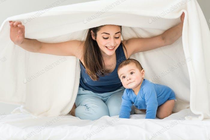Retrato de madre feliz con su hijo jugando bajo manta blanca en casa