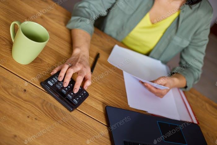 Cerca de la mujer sentarse calcular los gastos en la calculadora en la mesa de madera