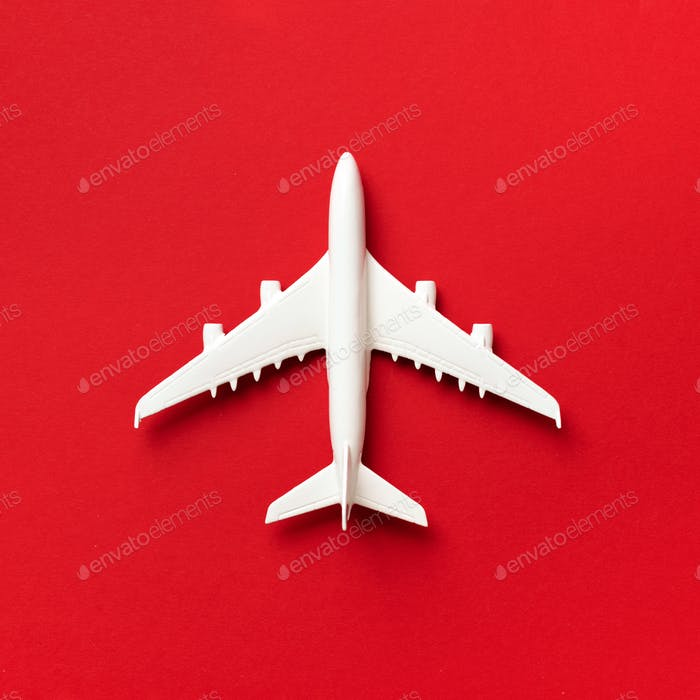 Travel, vacation concept. White model airplane on red color background with copy space. Top view