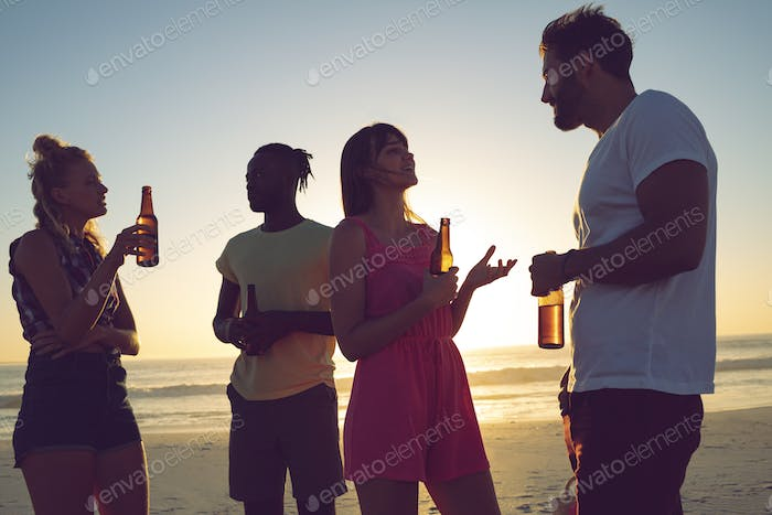 Side view of group of diverse friends having beer and interacting with each at beach during sunset