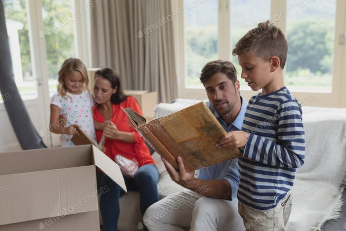 Side view of Caucasian family looking at photo album in living room at home