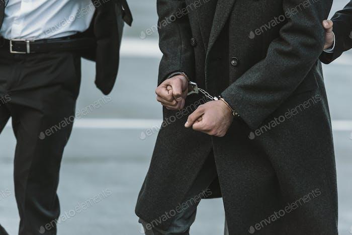 Imagen recortada del guardia de seguridad sosteniendo al hombre esposado