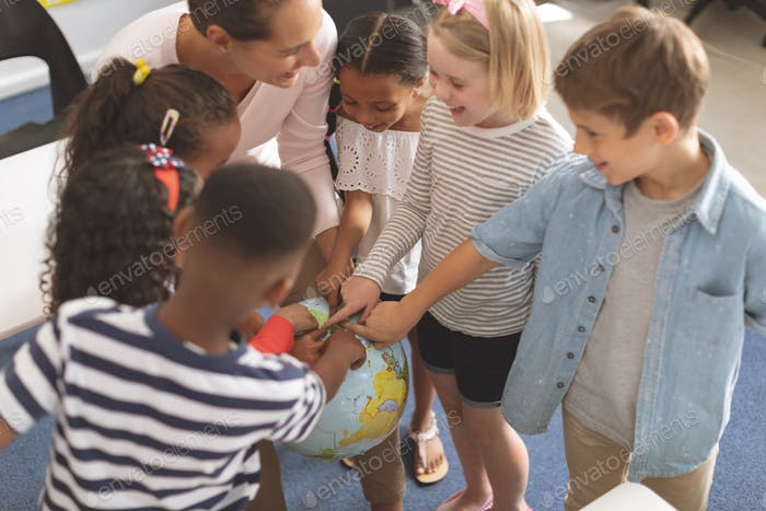 Schoolteacher discussing over earth globe in classroom while she is laughing with his school kids