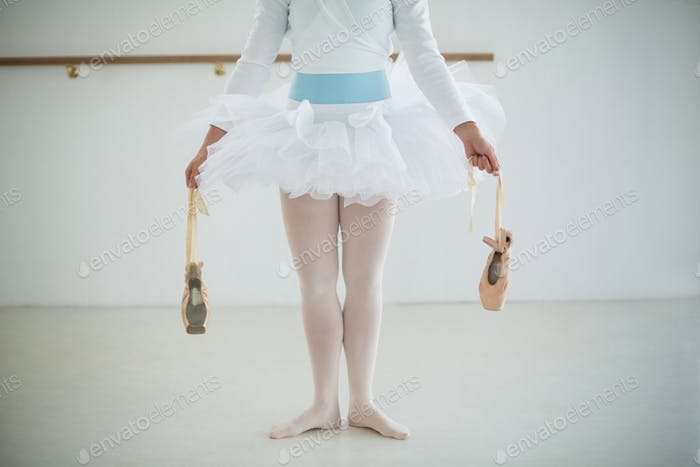 Low section of ballerina holding ballet shoes