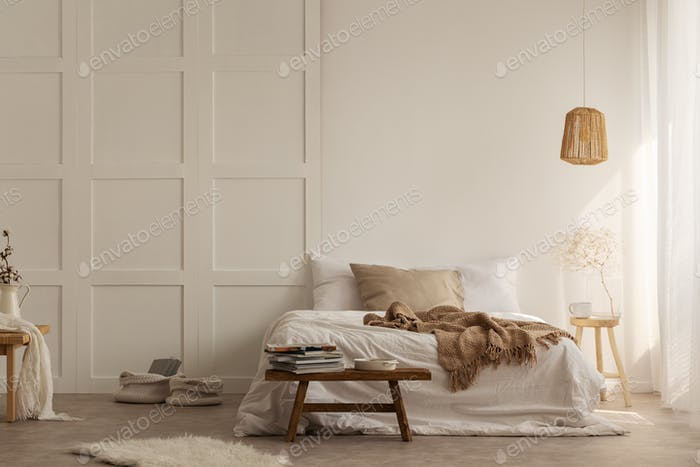 Natural blanket on white bed in simple bedroom interior with fur