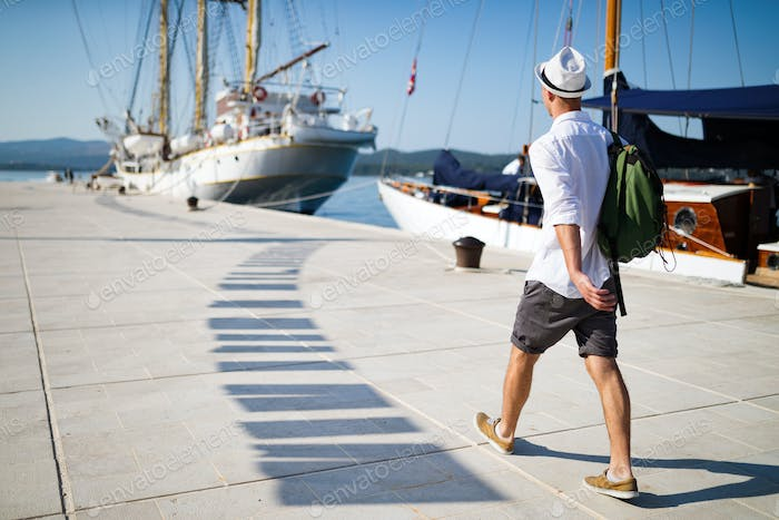 Vacation, holidays, travel, sea and people concept. Man with backpack enjoying travelling
