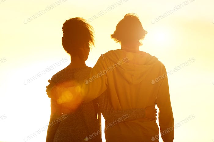 Young couple embracing looking at sunset