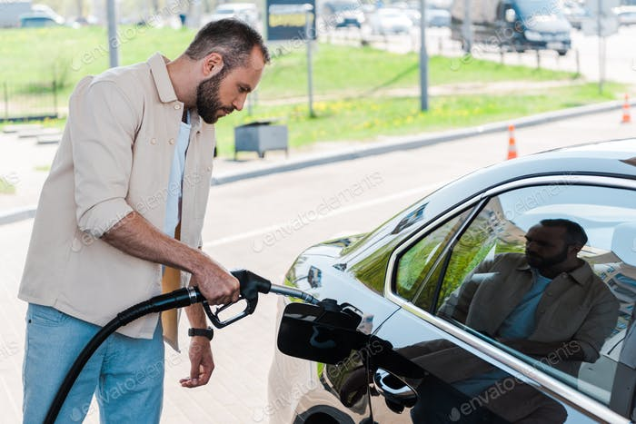 handsome man holding fuel pump and refueling black car at gas station