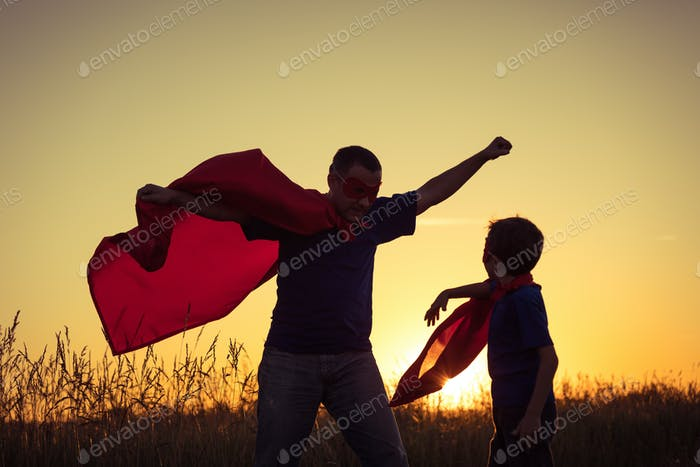 Father and son playing superhero at the sunset time.