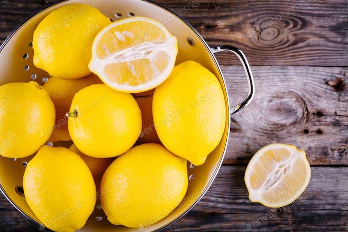 frische Bio-Zitronen in einem Sieb auf einem hölzernen Hintergrund. Ansicht von oben