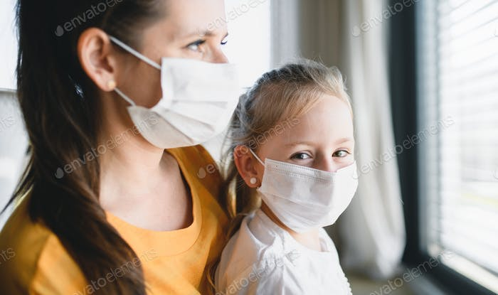 Mother and child with face mask indoors at home, Corona virus and quarantine concept