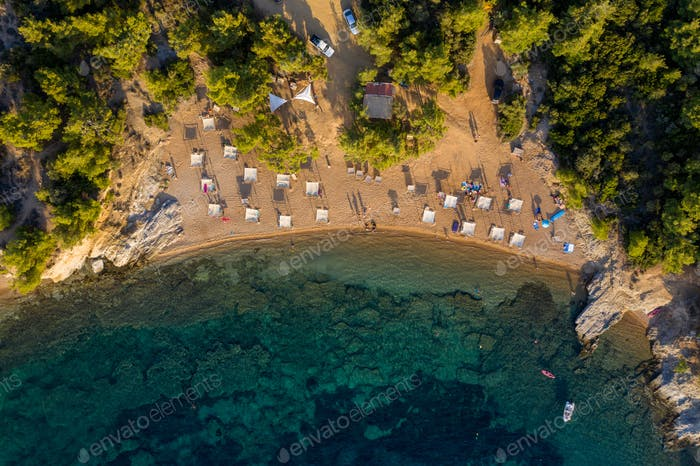 Aerial drone view of beach umbrellas and sunbeds on the coast in Thassos island, Greece