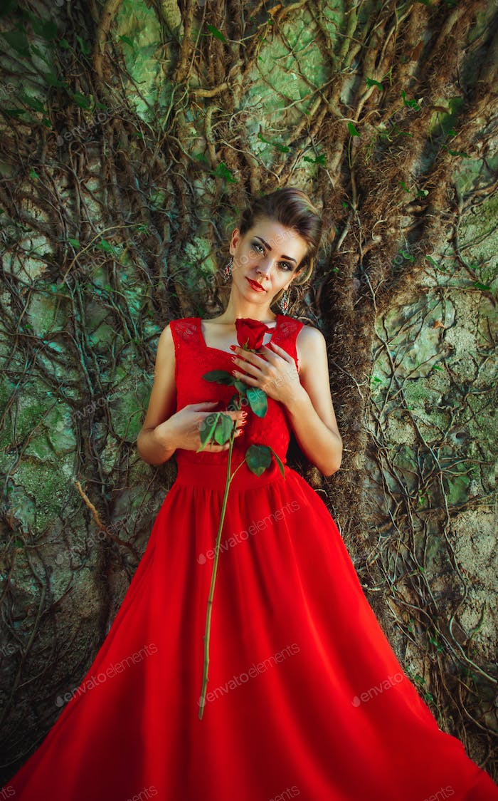 Beautiful woman in a red dress with a rose in hand on background