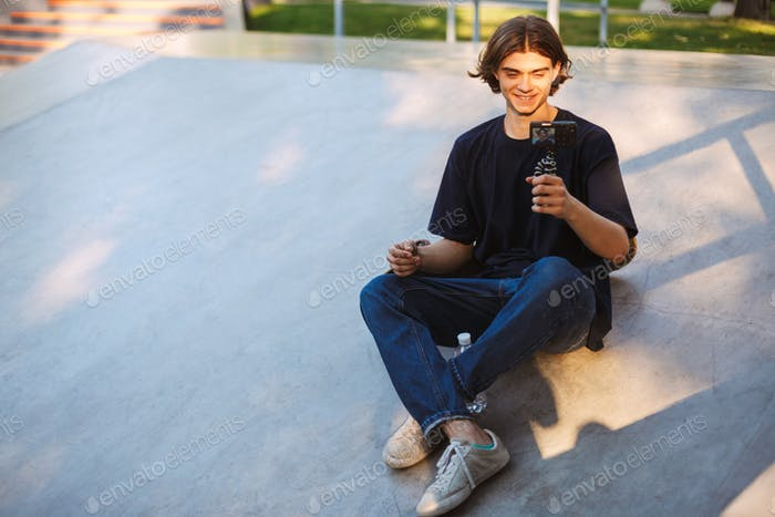 Young joyful  skater happily recording new video for vlog while