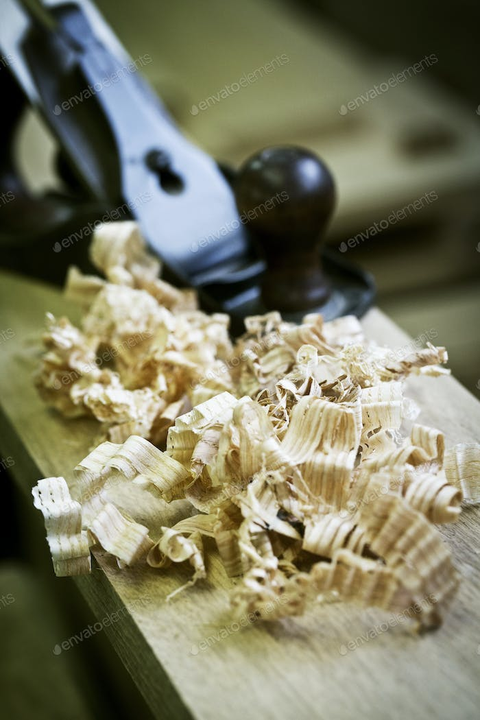 A wood plane on a piece of wood and wood shavings.