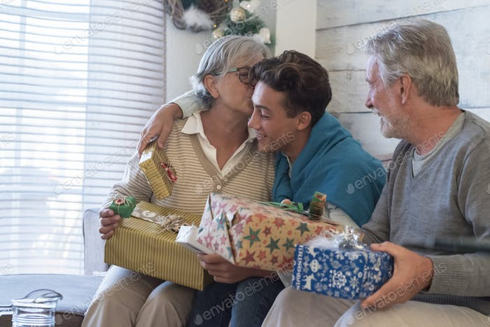 Group of people grandfathers and young grandson celebrate christmas night at home with gifts