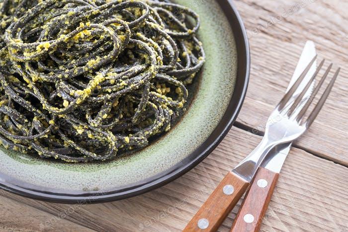 Black pasta with pesto sauce