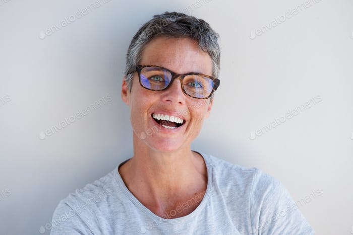 Close up attractive older woman smiling with glasses against white background