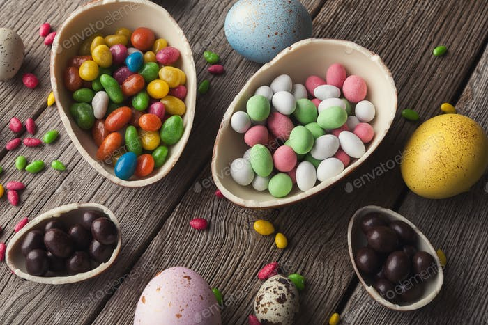 Colorful easter eggs and sprinkles on black background
