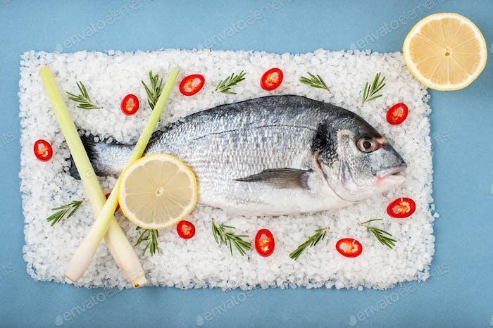 Fresh Dorado Fish with rosemary, chili pepper and lemon on a sal