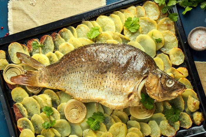 Baked carp, whole fish from the oven with sliced potatoes on a large tray. Traditional polish dish