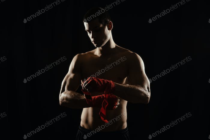 Portrait of a boxer bandaging hands