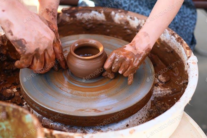 Hände arbeiten auf Töpferrad