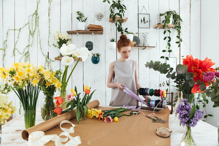Young lady holding ribbon to make bouquet in workshop