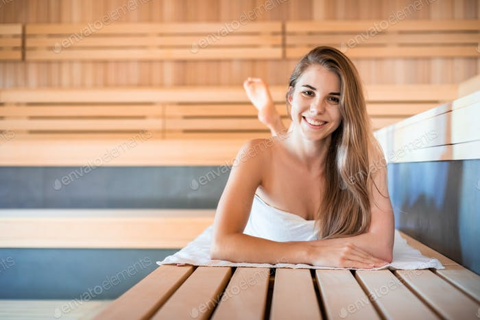 Welcome to sauna young woman relaxing and looking at camera