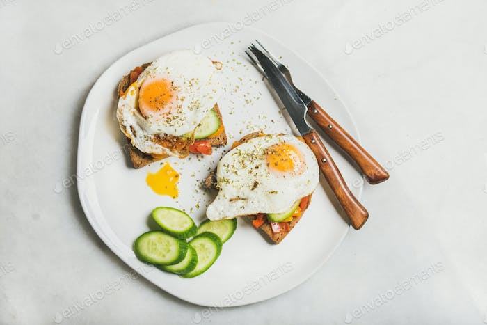 Breakfast toast with fried eggs and vegetables, top view
