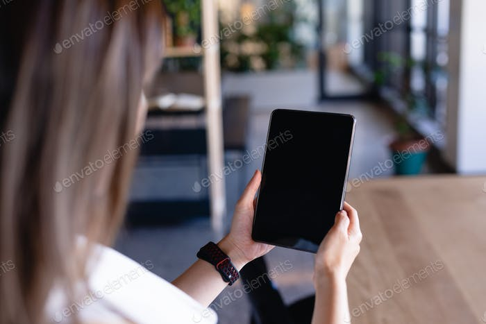 Focus on a digital tablet holding by a woman
